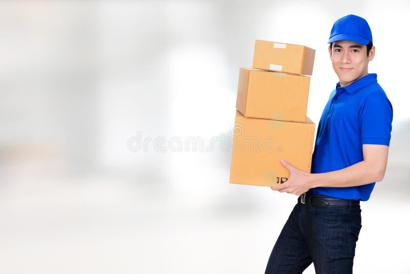 Усмехаясь коробка нося пакета работника доставляющего покупки на дом стоковые фото