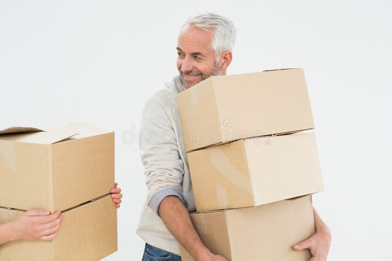Усмехаясь коробки нося зрелого человека стоковые изображения rf