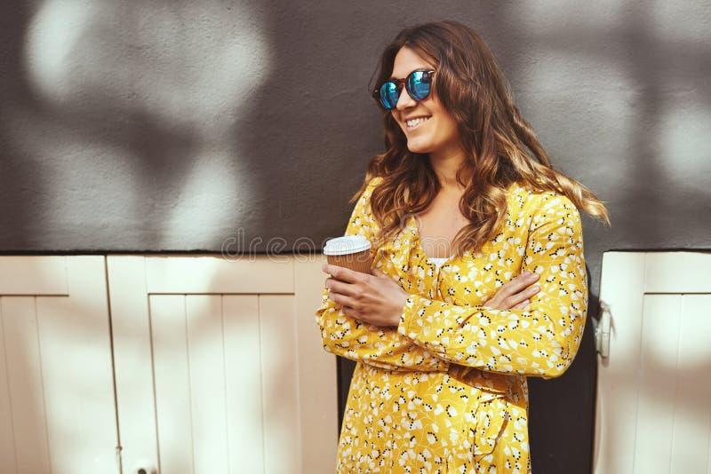 Усмехаясь кофе молодой женщины брюнета выпивая в городе стоковые изображения rf