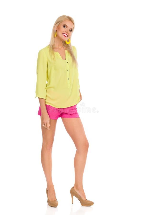 Усмехаясь красивая белокурая женщина в живых одеждах и высоких адах стоящ и смотрящ камера стоковое фото rf