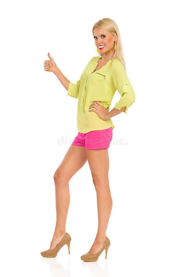 Усмехаясь красивая белокурая женщина в живых одеждах и высоких адах стоящ и показывающ большой палец руки вверх стоковые фото