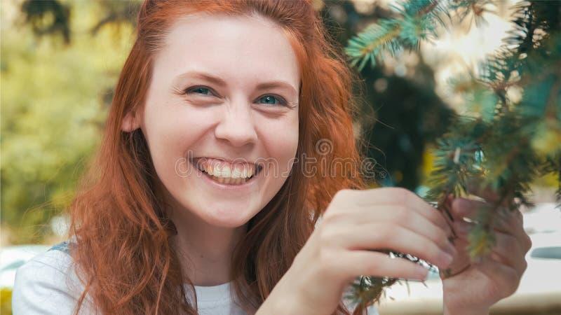 Усмехаясь красивая девушка имбиря в зеленом парке стоковые фото