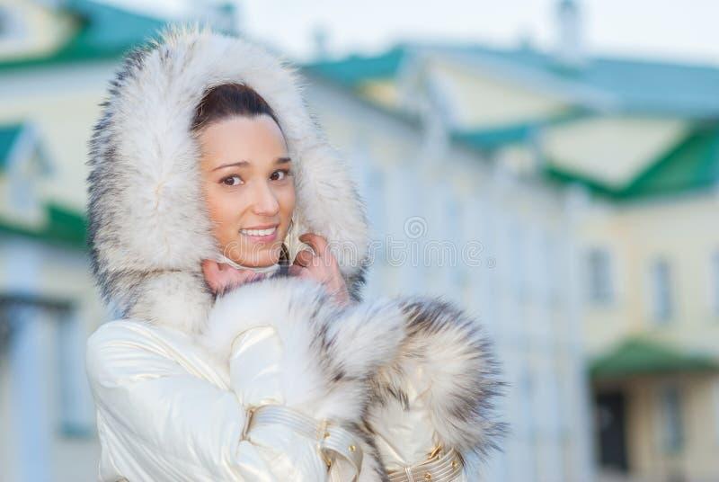 Усмехаясь красивая женщина в белом пальто стоковые фото