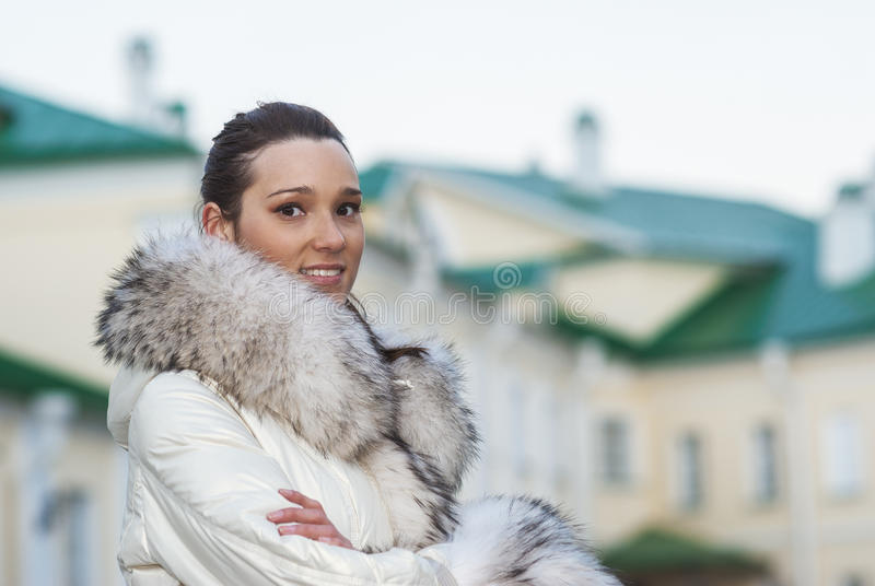 Усмехаясь красивая женщина в белом пальто стоковая фотография