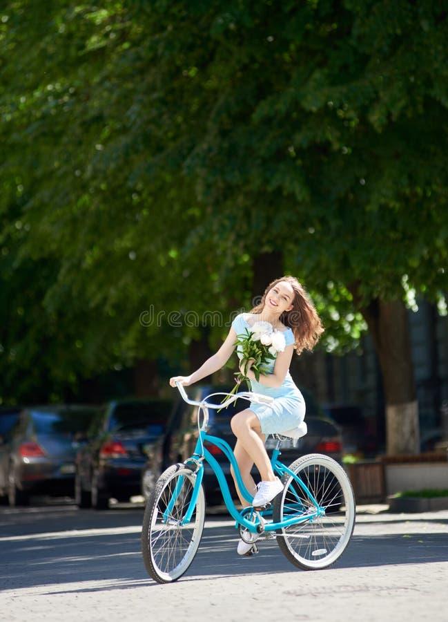 Усмехаясь красивая женщина держа пионы и ехать голубая улица велосипеда вниз пустая вымощенная с зелеными деревьями вокруг стоковое изображение rf