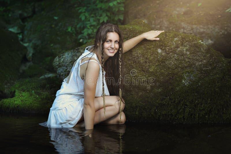 Усмехаясь красивая женщина представляя в потоке стоковое фото