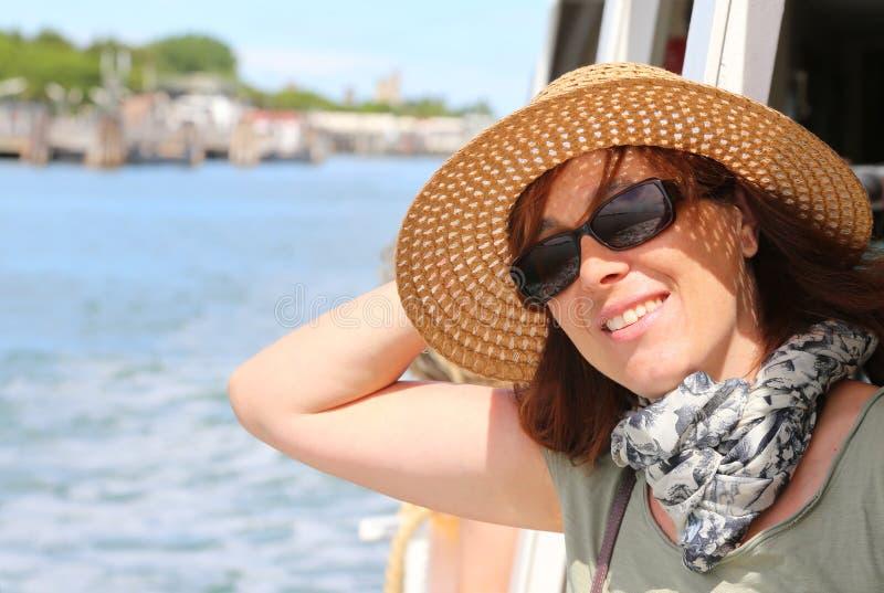 Усмехаясь красивая женщина с стеклами соломенной шляпы и солнца стоковое изображение