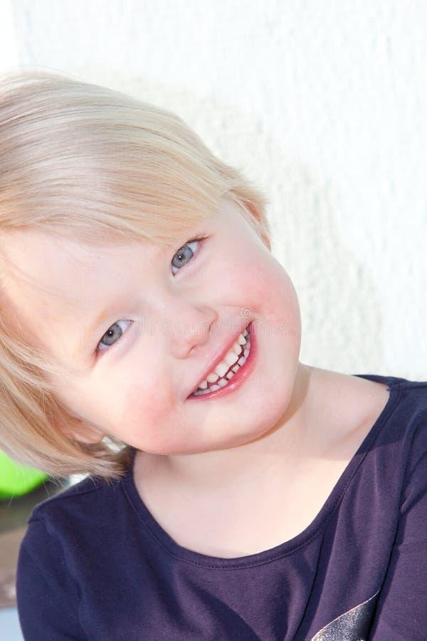 Усмехаясь красивая маленькая белокурая девушка стоковое фото rf