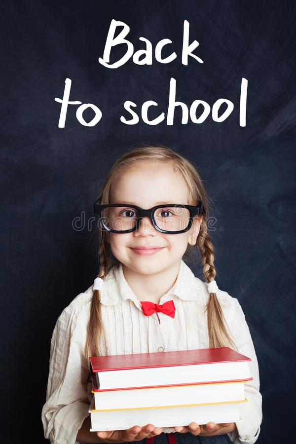Усмехаясь красивая милая маленькая девочка держа книги стоковые фото