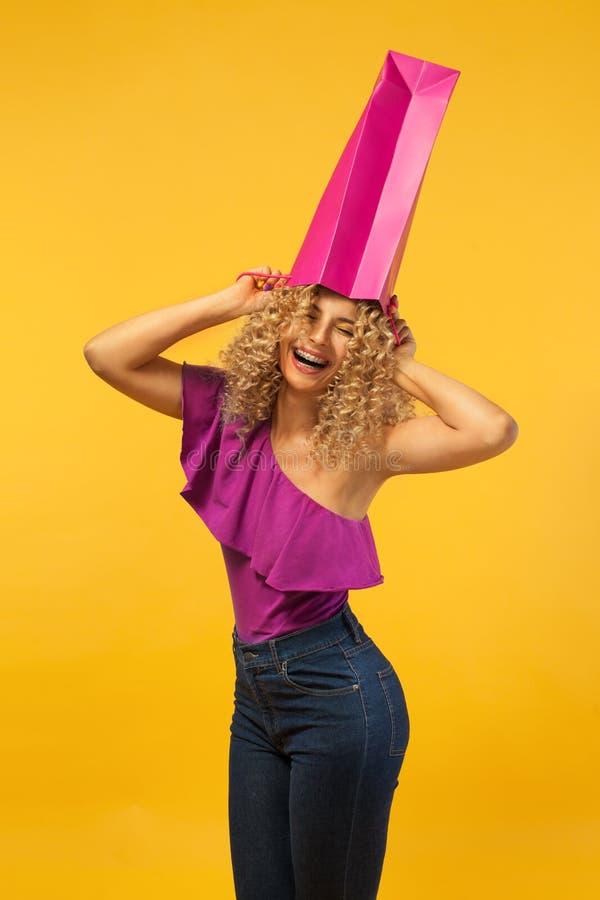 Усмехаясь красивая молодая женщина с сумками Девушка с афро стилем причесок и расчалками Желтая предпосылка Концепция для продажи стоковая фотография