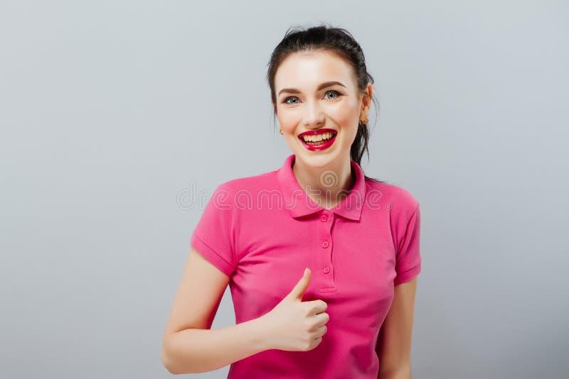 Усмехаясь красивая молодая женщина в розовом мини платье показывая большой палец руки вверх и подмигивать стоковое фото rf