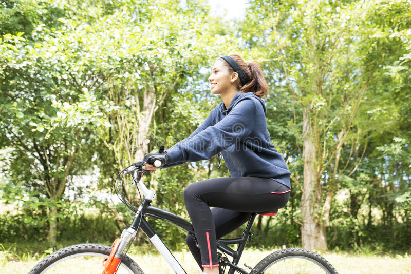 Усмехаясь красивая молодая женщина работая с велосипедом, внешним стоковые изображения