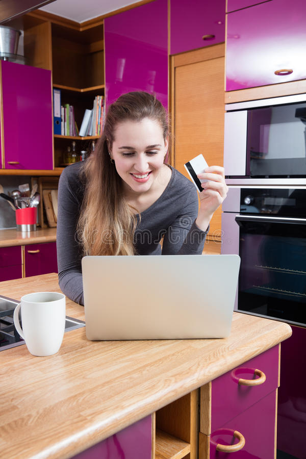 Усмехаясь красивая молодая женщина ходя по магазинам и покупать онлайн от дома стоковое изображение