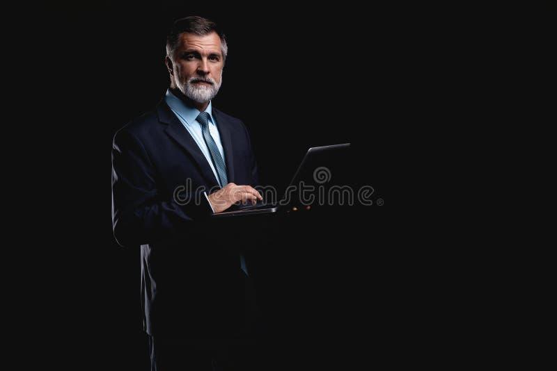 Усмехаясь красивый бизнесмен работая с компьтер-книжкой Изолировано над черной предпосылкой стоковые фото