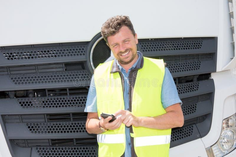 усмехаясь красивый водитель работника доставляющего покупки на дом перевозит смотреть на грузовиках его smartphone app для постав стоковые фотографии rf
