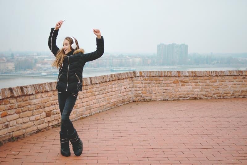 Усмехаясь красивый девочка-подросток слушает к музыке и танцует с руками вверх по снаружи стоковое фото rf