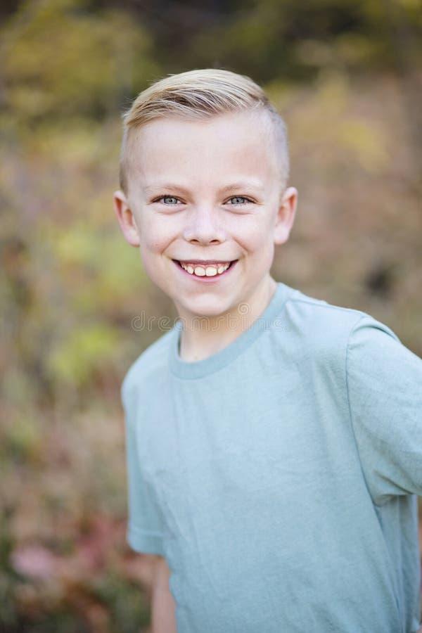 Усмехаясь красивый мальчик играя outdoors и смотреть камеру стоковые фотографии rf