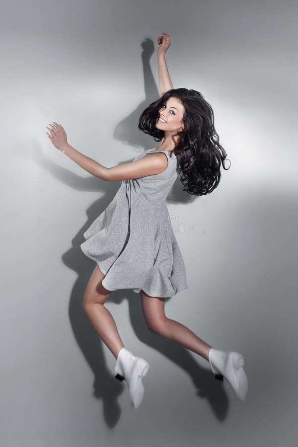 Усмехаясь красивый скакать женщины брюнет стоковая фотография rf