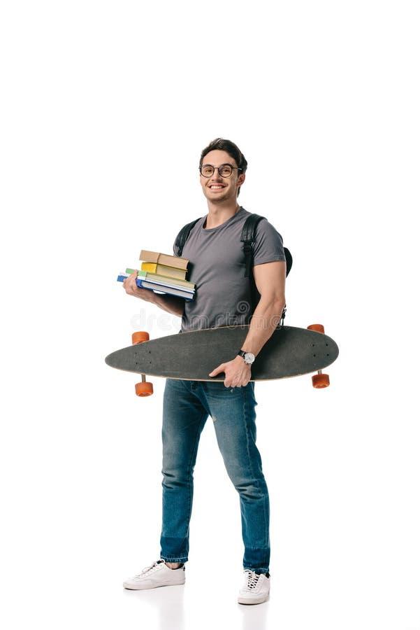 усмехаясь красивый студент держа книги и конек стоковое изображение rf