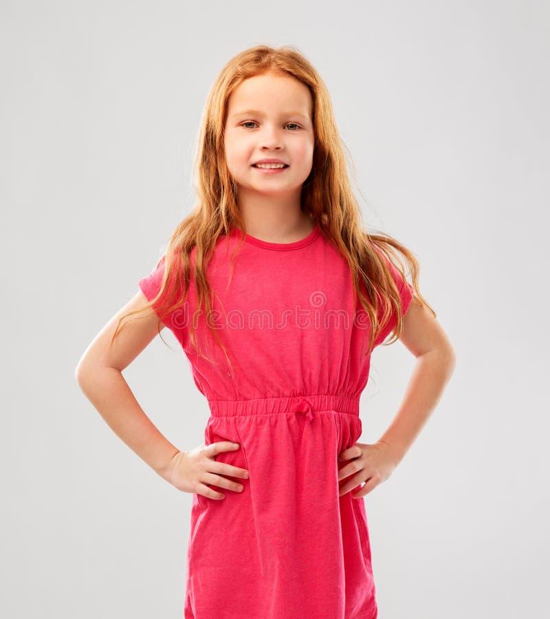 Усмехаясь красная с волосами девушка представляя в розовом платье стоковое изображение rf