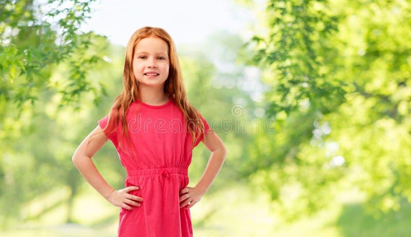Усмехаясь красная с волосами девушка представляя в розовом платье стоковая фотография rf