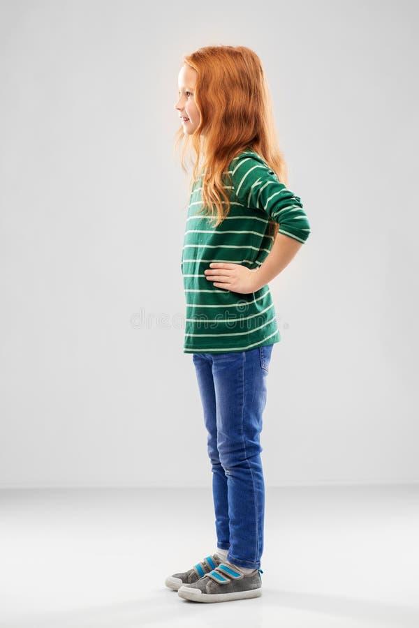 Усмехаясь красная с волосами девушка представляя в striped рубашке стоковое фото rf