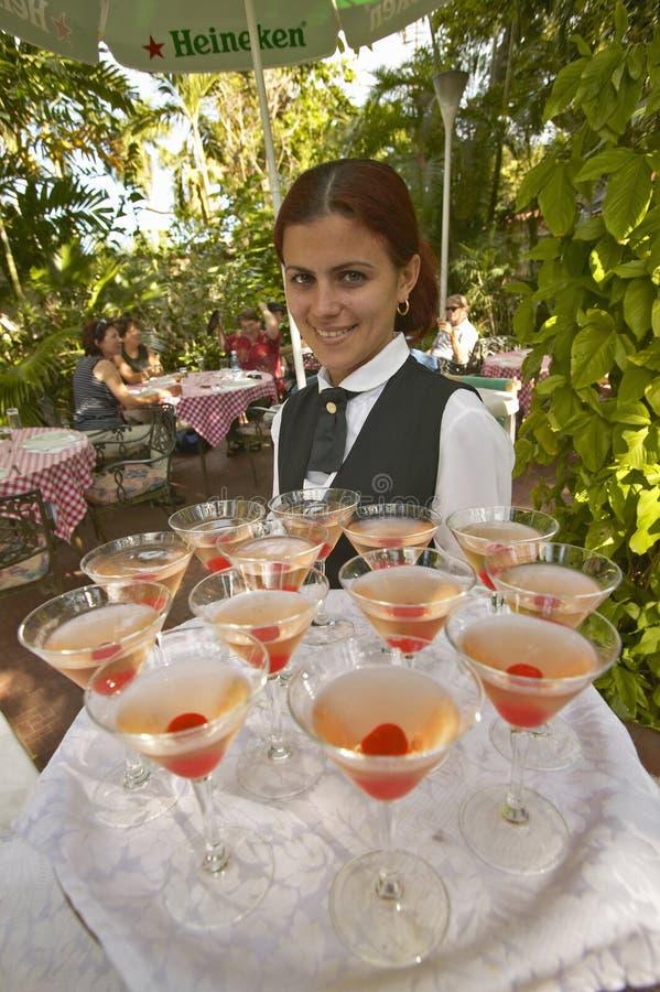 Усмехаясь кубинськая женщина предлагая поднос пить на туристском ресторане в Гаване Кубе стоковое фото rf