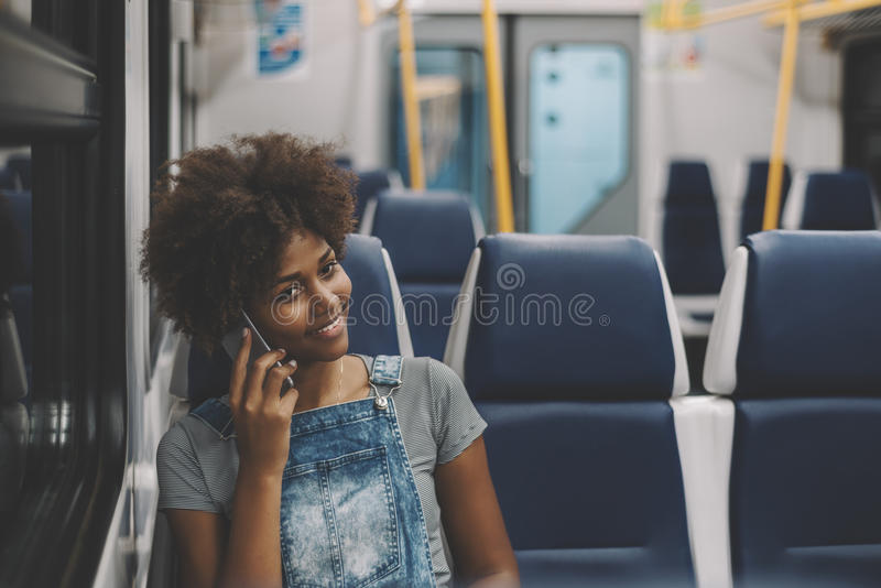Усмехаясь курчавая черная девушка в поезде используя умный телефон стоковое изображение rf