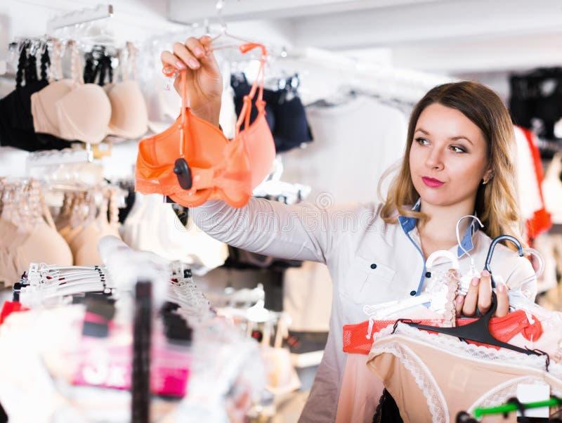 Усмехаясь клиент молодой женщины выбирая женское бельё стоковые фотографии rf