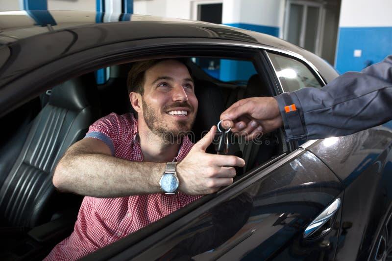 Усмехаясь клиент принимает ключ стоковое фото
