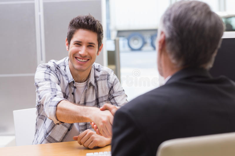 Усмехаясь клиент тряся руку продавца стоковые изображения