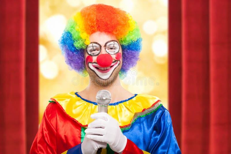 Усмехаясь клоун используя микрофон стоковые изображения