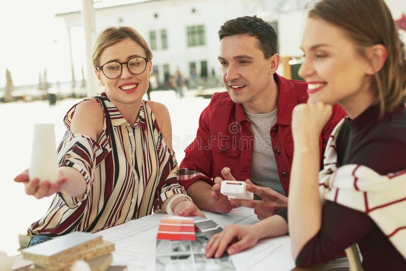 Усмехаясь люди ища новая мебель в будущем интерьере стоковое изображение rf