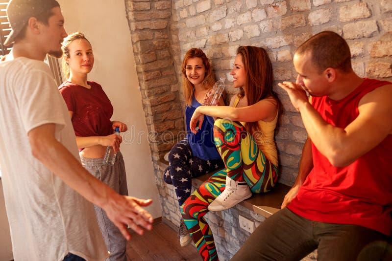 Усмехаясь люди наслаждаясь на проломе на танцах в студии стоковая фотография