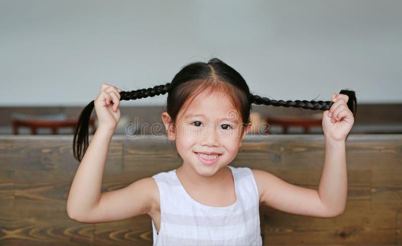 Усмехаясь маленькая азиатская девушка держа ее волосы отрезков провода лежа на деревянной таблице со смотреть камеру стоковые фотографии rf