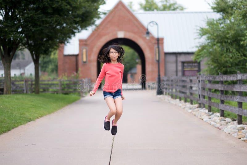 Усмехаясь маленькая азиатская девушка скачет вверх в парк стоковые изображения