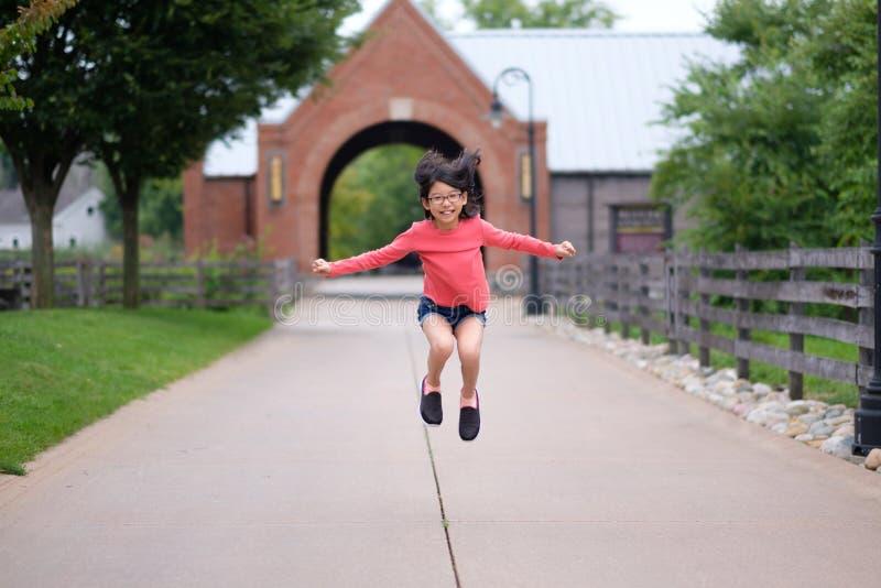 Усмехаясь маленькая азиатская девушка скачет вверх в парк стоковое фото rf