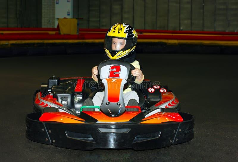 усмехаясь маленькая девочка в шлеме в идет-kart на karting след стоковая фотография rf