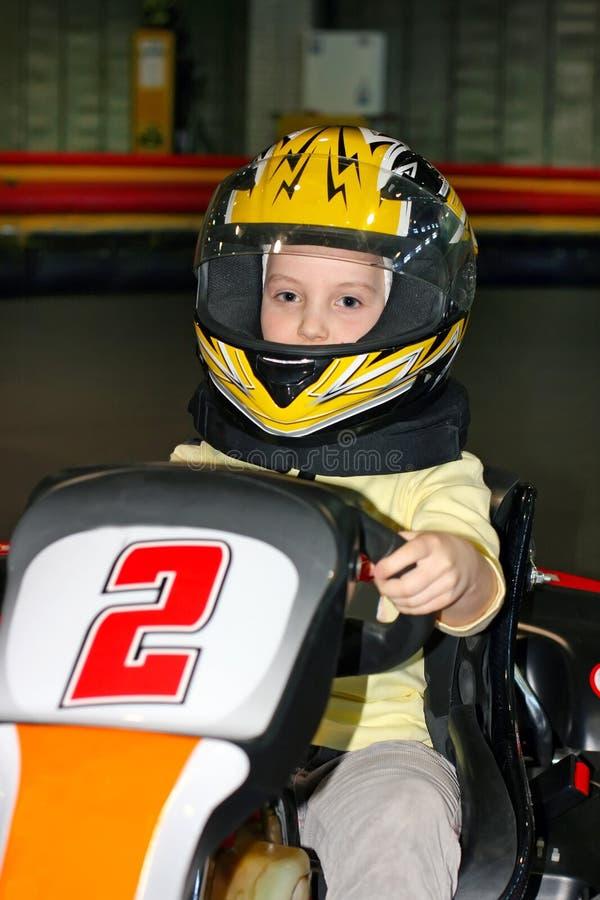 усмехаясь маленькая девочка в шлеме в идти-kart на kart стоковая фотография