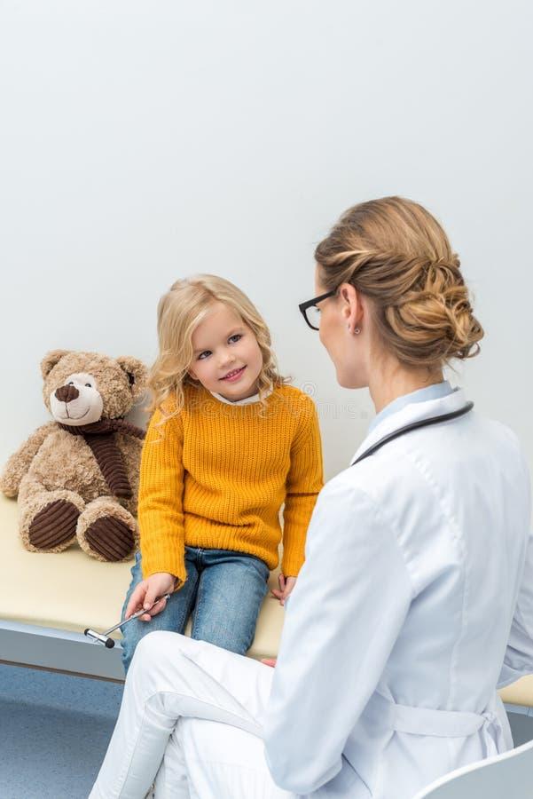 усмехаясь маленькая девочка делая рассмотрение неврологии стоковые изображения