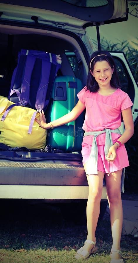 Усмехаясь маленькая девочка нагружает автомобиль с багажом стоковая фотография rf