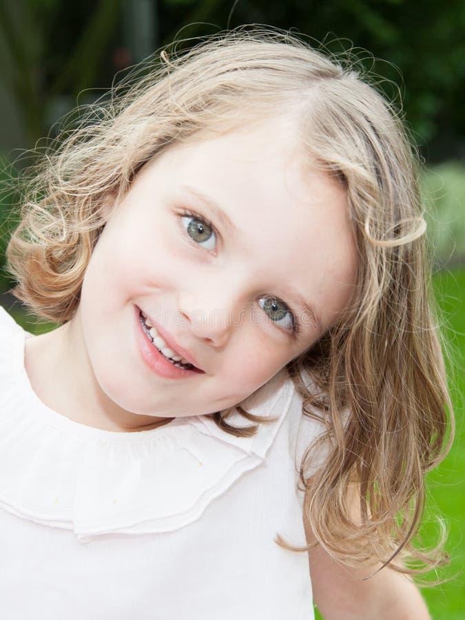 Усмехаясь маленькая девочка сидя на траве в летнем дне внешнем стоковое изображение rf
