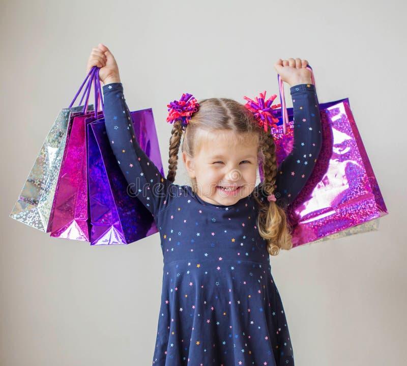 Усмехаясь маленькая девочка с хозяйственными сумками с подарками стоковые изображения