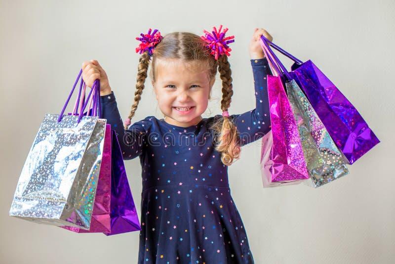 Усмехаясь маленькая девочка с хозяйственными сумками черное сбывание пятницы стоковые изображения rf