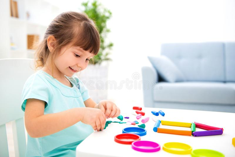 Усмехаясь маленькая красивая девушка ваять новый дом пластилина Творческие способности детей детство счастливое Мечты новоселья стоковые фотографии rf