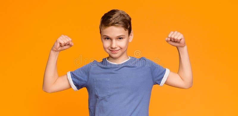 Усмехаясь мальчик демонстрируя его бицепс и мышцы стоковое фото rf