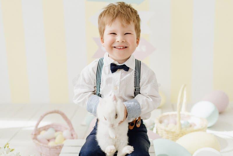 Усмехаясь мальчик играя с кроликом пасхи стоковые фотографии rf