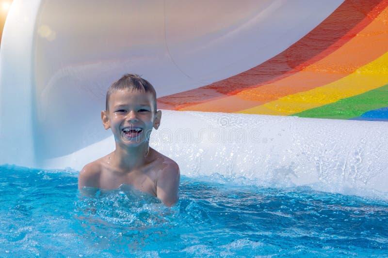 Усмехаясь мальчик имеет потеху в бассейне водными горками в парке aqua стоковое фото