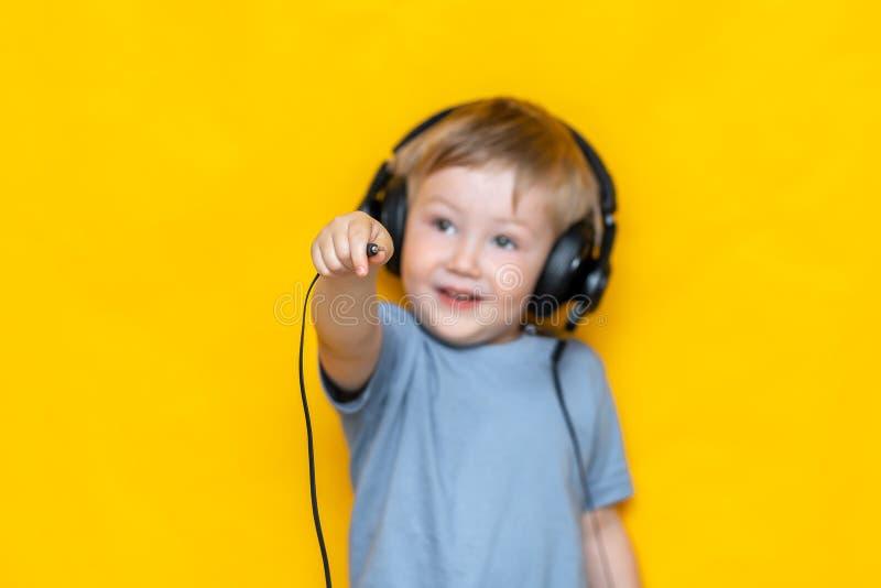 Усмехаясь мальчик отключить его наушники и штепсельную вилку шоу к камере на изолированной желтой предпосылке стоковые изображения rf