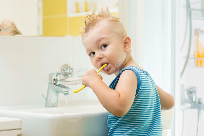 Усмехаясь мальчик ребенк ребенка чистя щеткой и чистые зубы себя в bathroom стоковое изображение